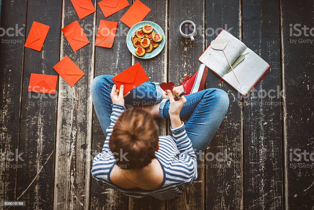 Young woman sending a valentine card - top view stock photo