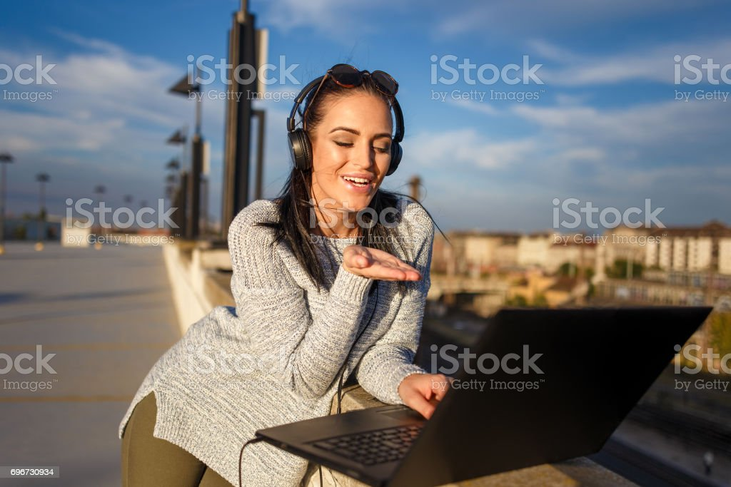 Young woman sending kiss online by laptop outdoor stock photo