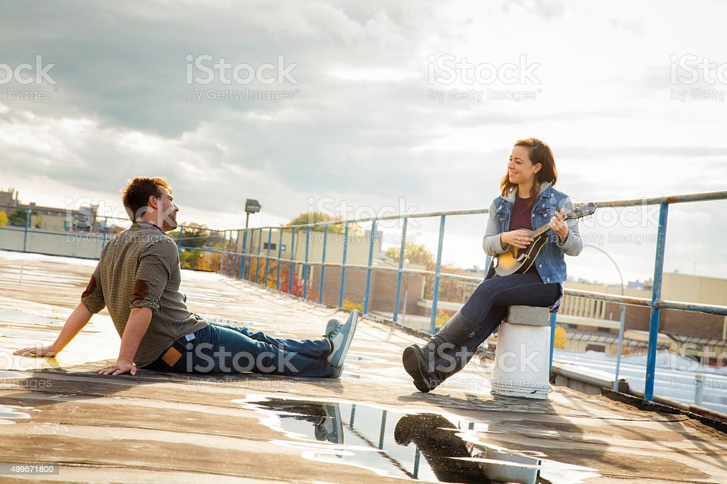 Young woman serenades her boyfriend on a rooftop after rainfall stock photo