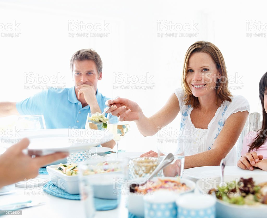 Young woman serving food with family having lunch royalty-free stock photo