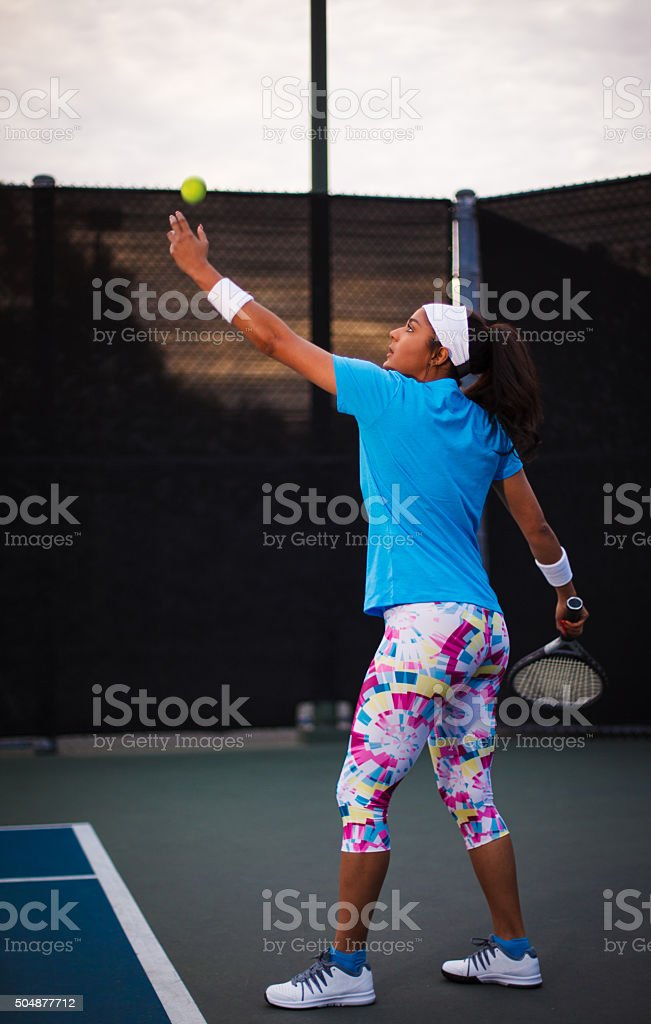 Young woman serving tennis ball on tennis court stock photo