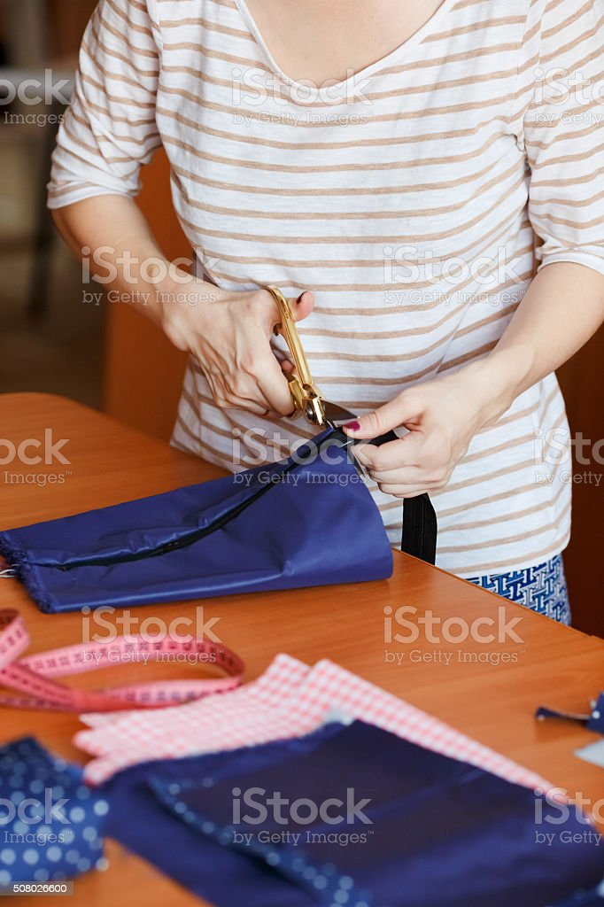 Young woman sewing at home, hemming blue fabric. Fashion designer stock photo