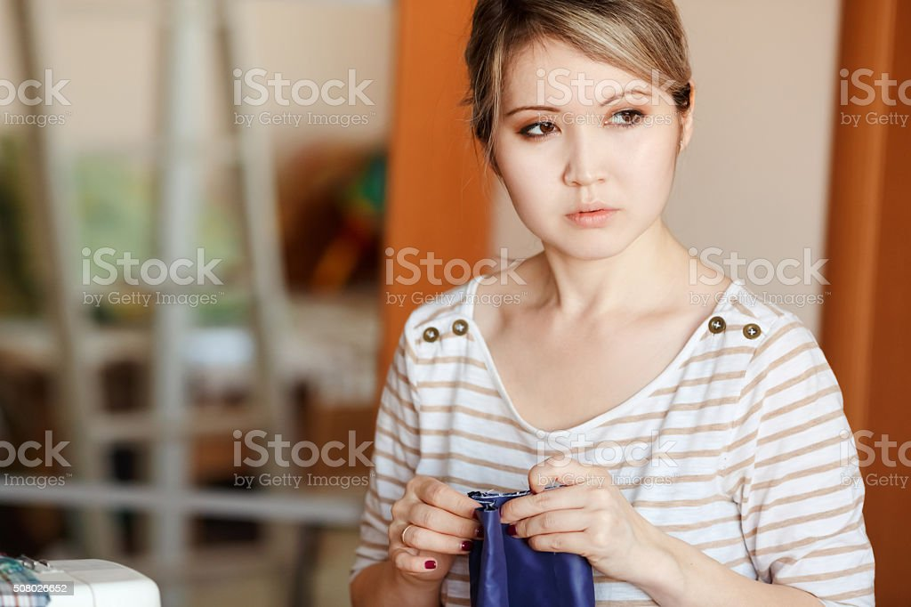 Young woman sewing at home, hemming blue fabric, stands and stock photo