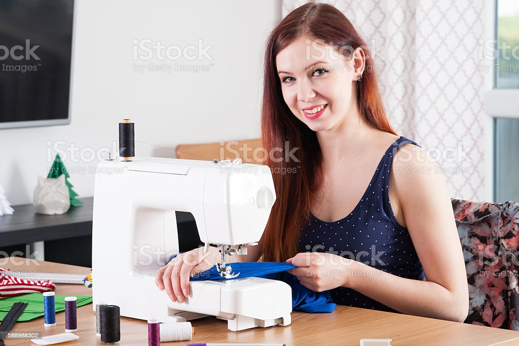 Young woman sewing fabric stock photo
