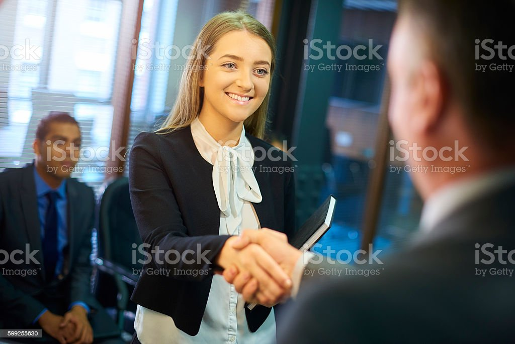 young woman shakes hands at interview stock photo