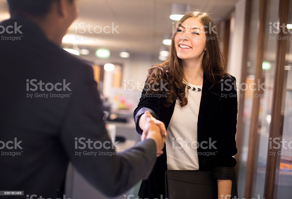 young woman shakes hands with her potential new boss stock photo
