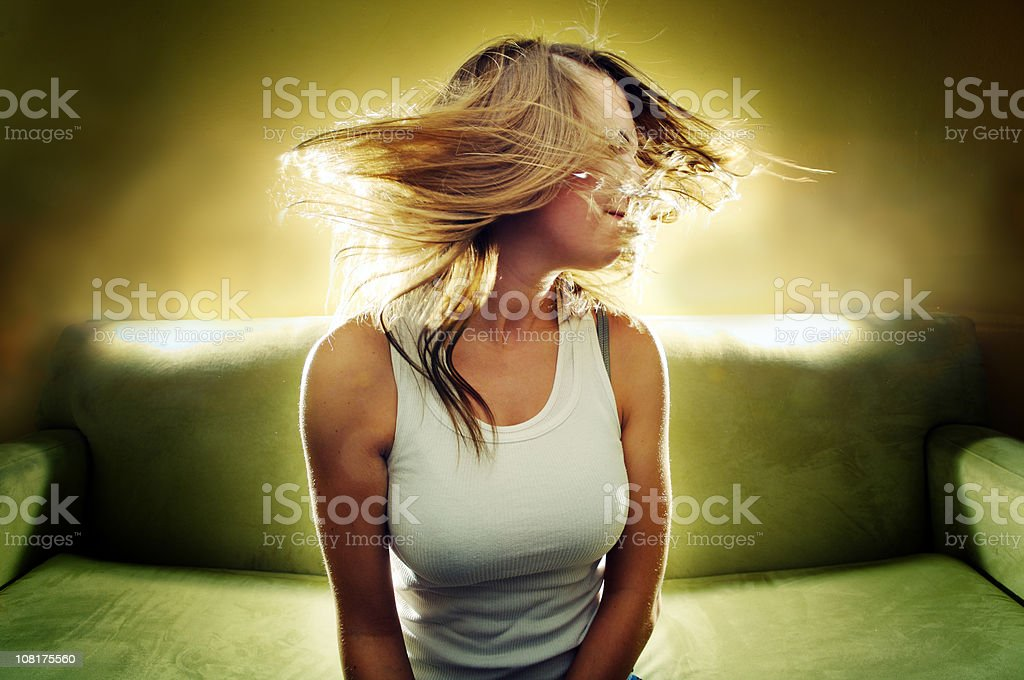 Young Woman Shaking Hair and Sitting on Couch royalty-free stock photo