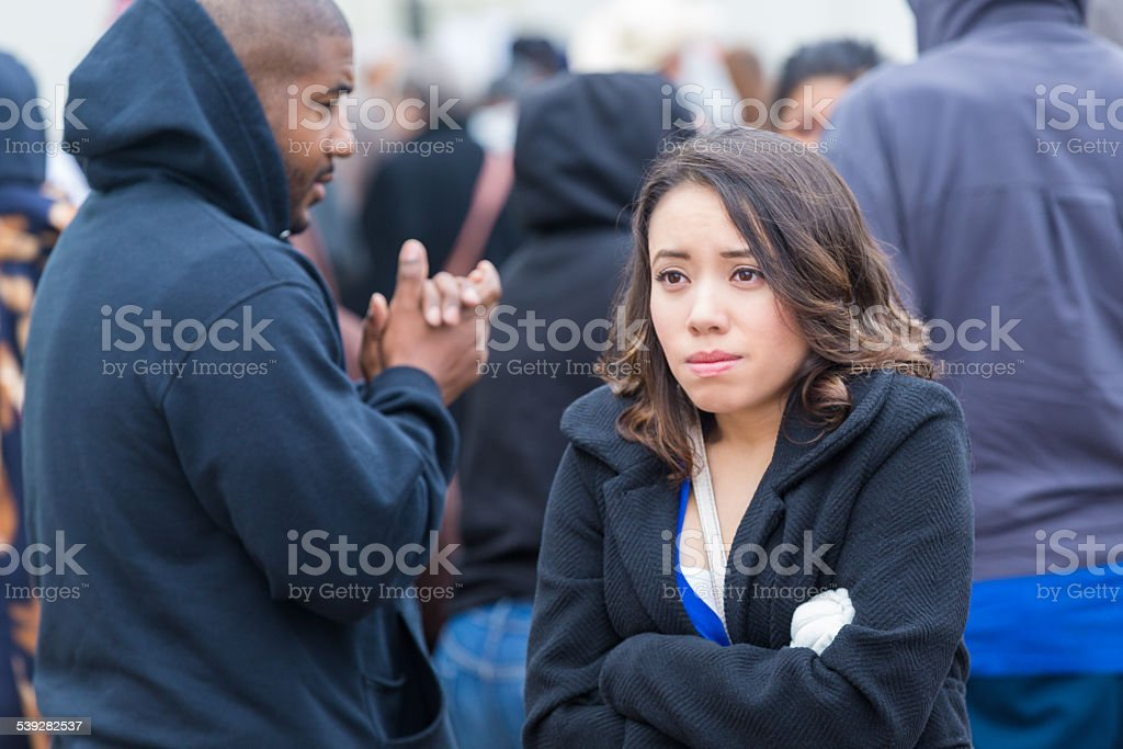 Young woman shivering outside in crowd on cold winter day stock photo