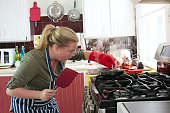 Young woman shocked at frying pan fire on stove top.
