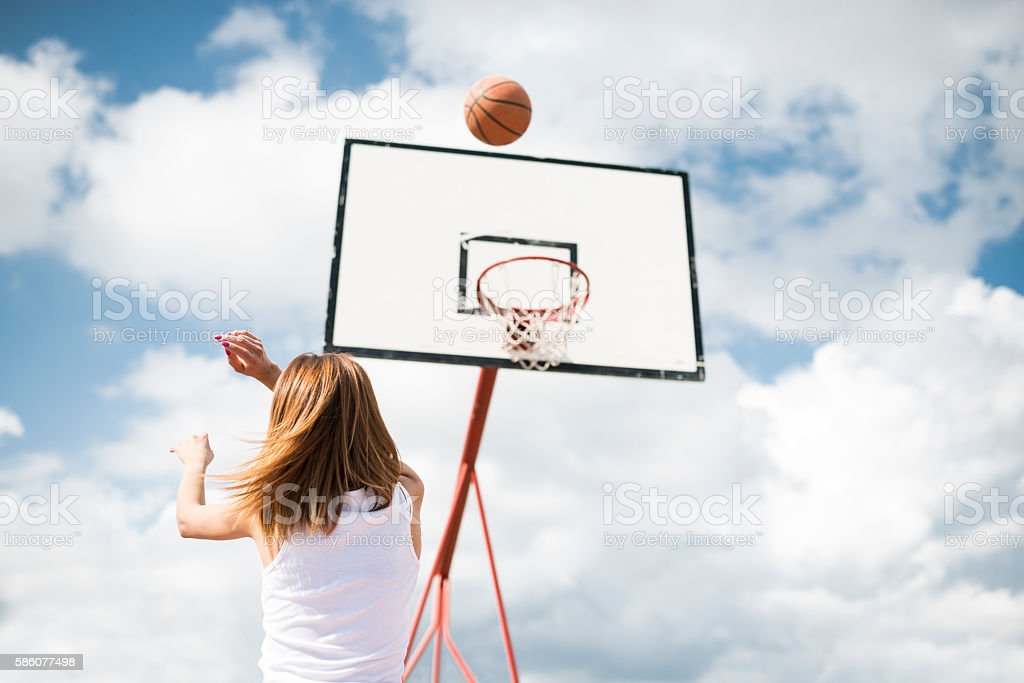 Young Woman Shooting at Basket on Outdoor Court stock photo
