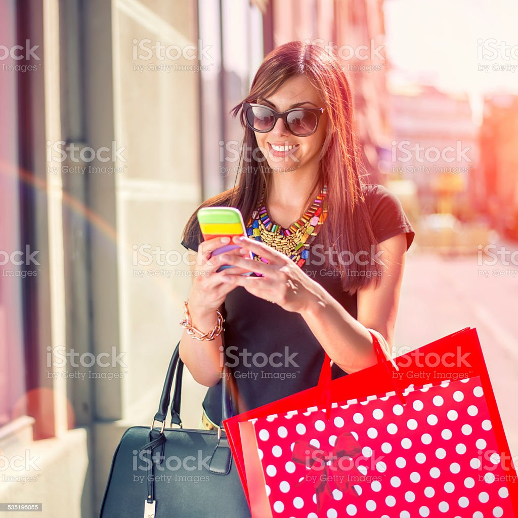 Young Woman Shopping and using mobile phone stock photo