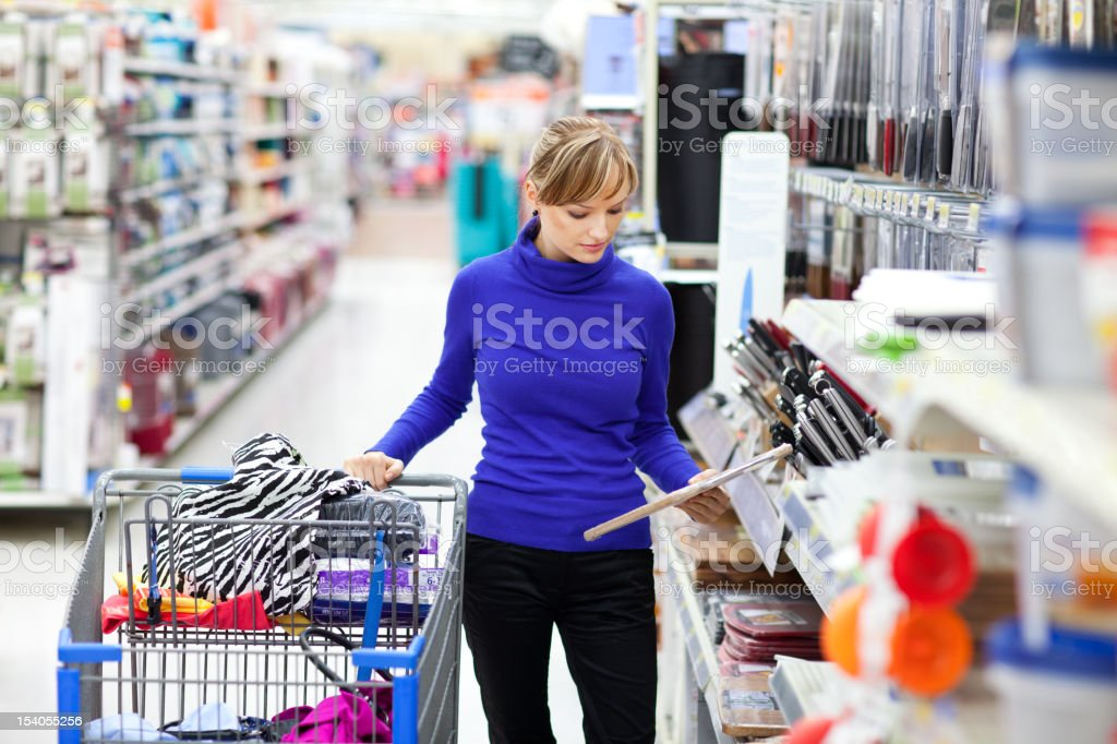 Young woman shopping at store checking label on product stock photo
