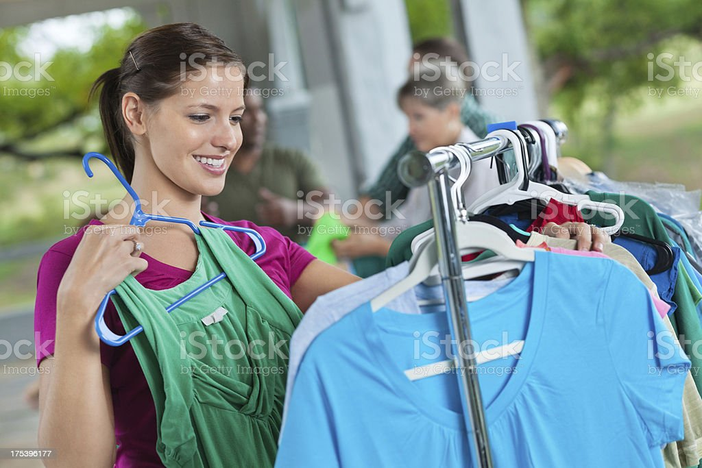 Young woman shopping at used clothing donation sale royalty-free stock photo