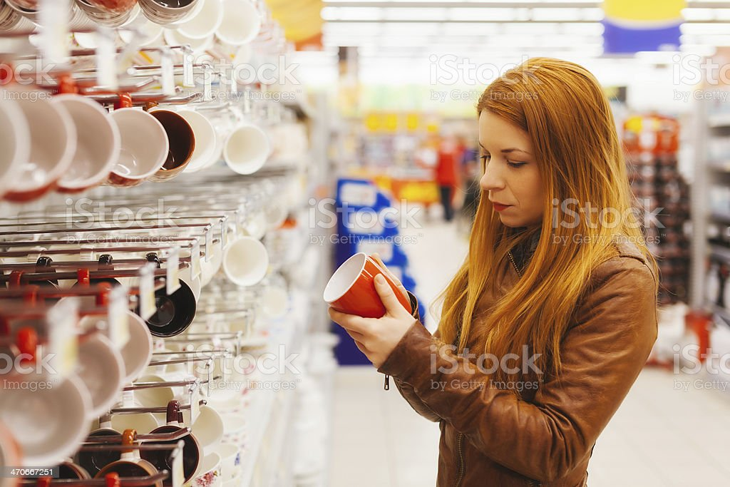 Young woman shopping for cup in supermarket stock photo