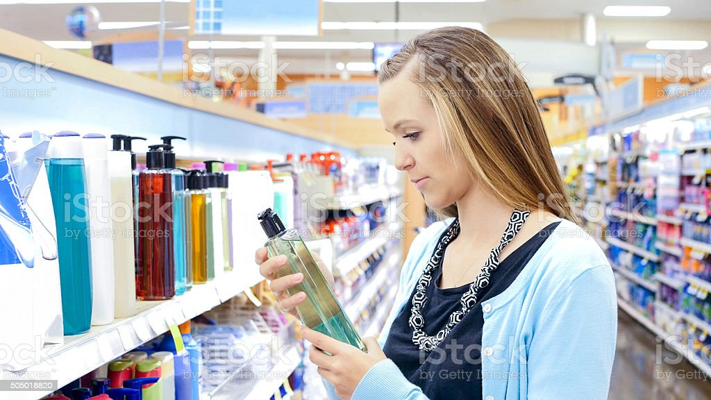 Young woman shopping for shampoo and beauty products in store stock photo