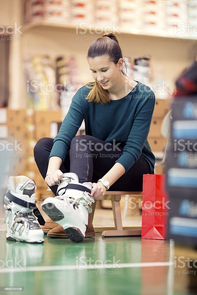 young woman shopping for ski boots stock photo