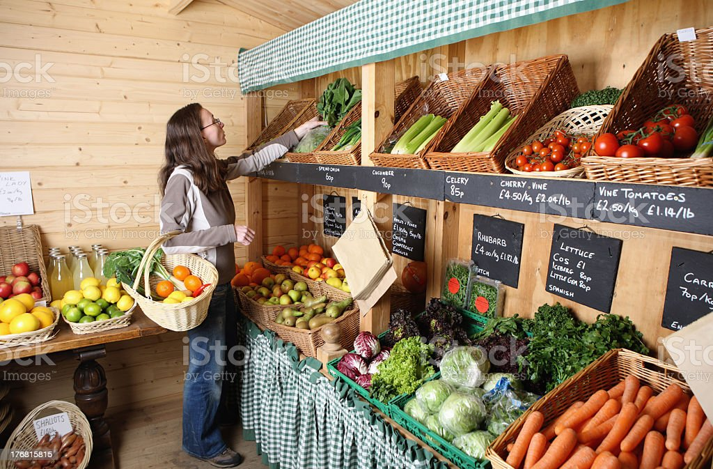 A young woman shopping for vegetables in the market royalty-free stock photo