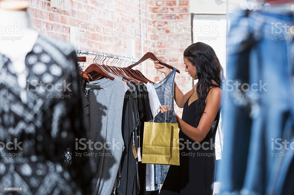 Young woman shopping in clothing store stock photo