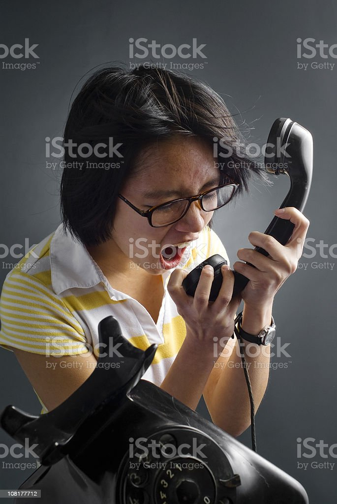 Young Woman Shouting into Phone royalty-free stock photo
