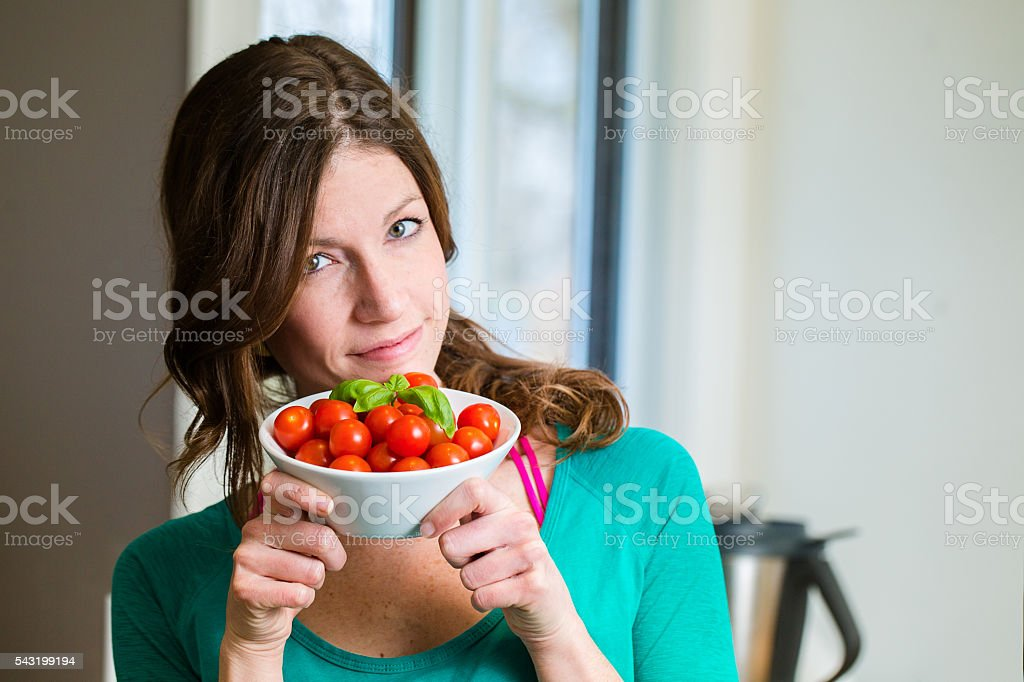 Young woman showing a cherry tomatoes bowl stock photo