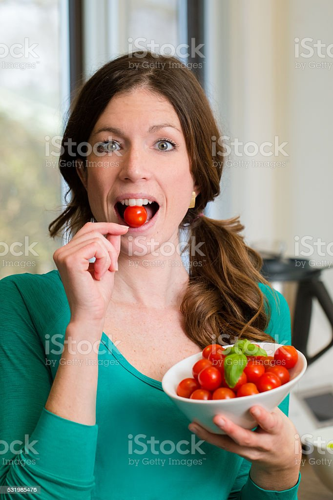 Young woman showing a cherry tomatoes in your mouth stock photo