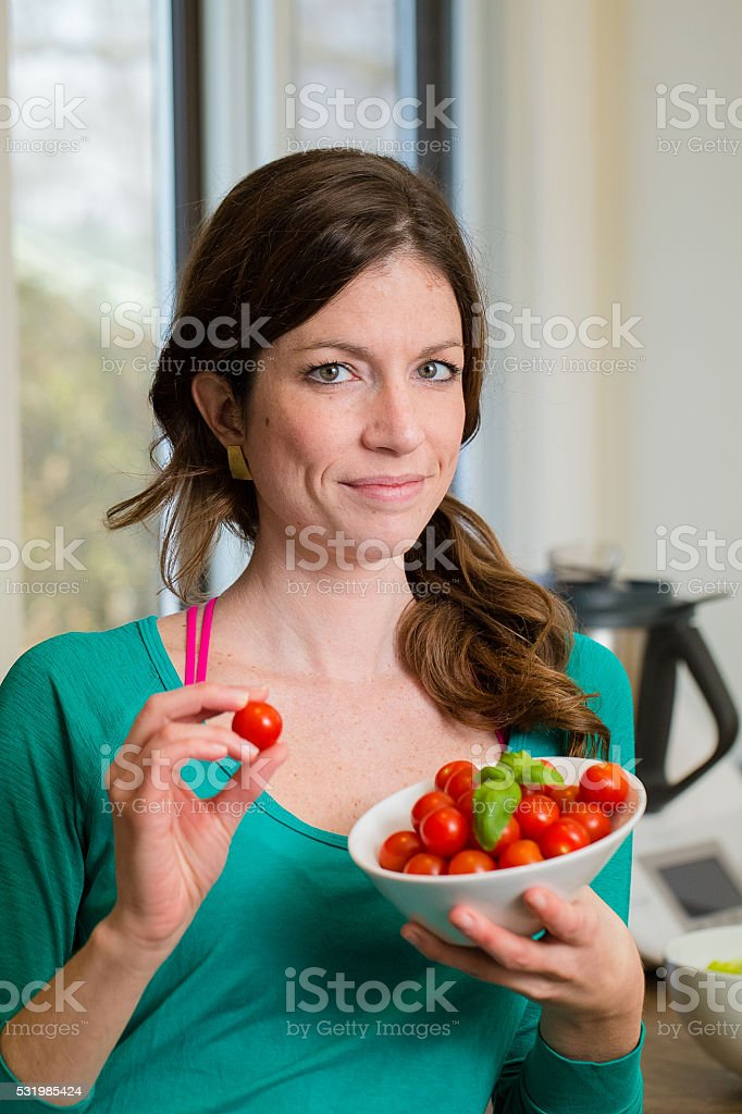Young woman showing a cherry tomatoes stock photo