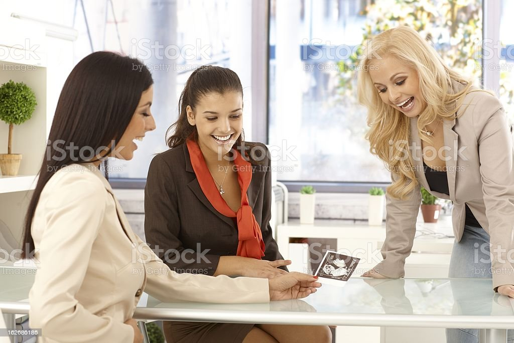 Young woman showing baby scan at office royalty-free stock photo