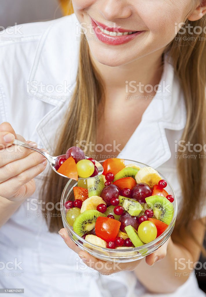 Young woman showing fresh raw fruit salad, smiling, posing indoors royalty-free stock photo