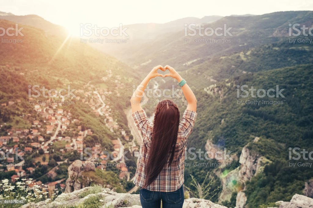 Young woman showing heart-shaped symbol stock photo