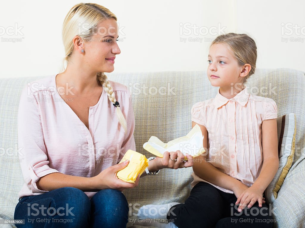 Young woman showing little daughter sanitary napking at home stock photo