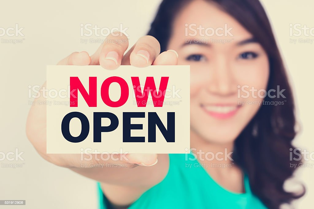 Young woman showing NOW OPEN sign stock photo