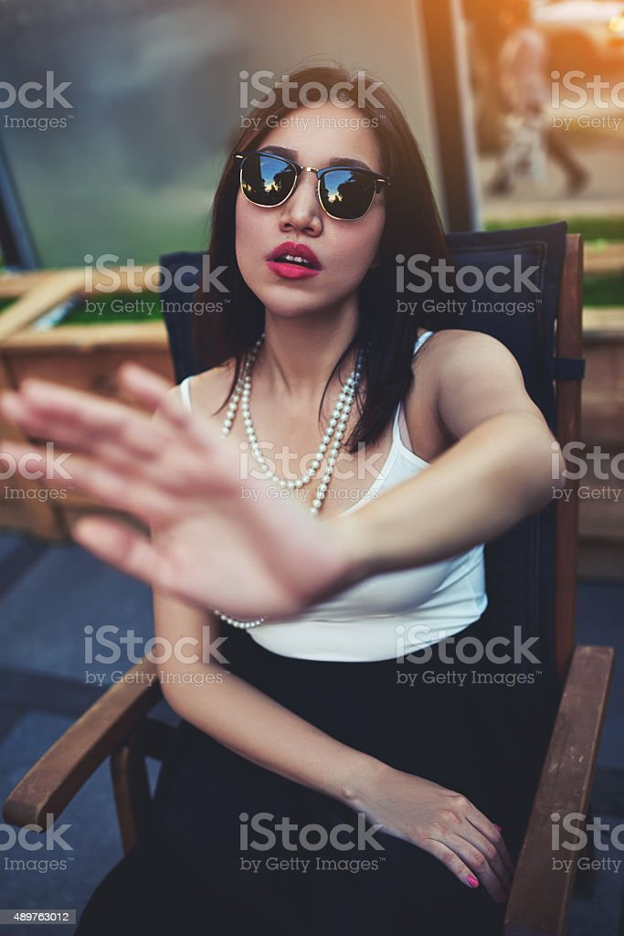 Young woman showing reluctance to be photographed stock photo