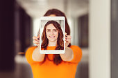 Young woman showing self portrait on tablet pc
