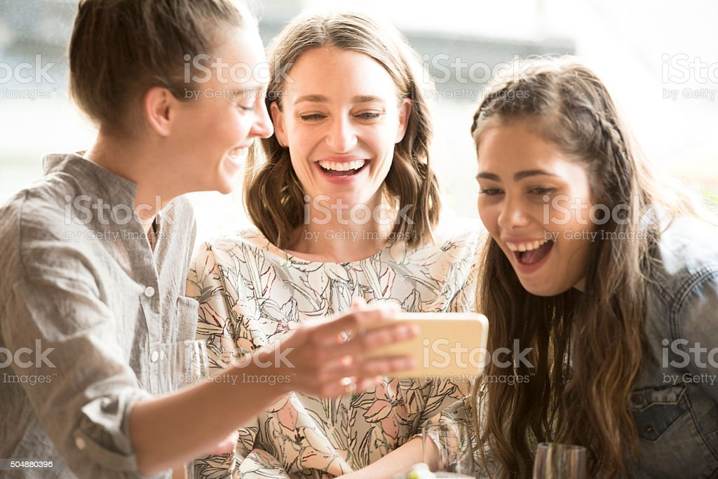 Young woman showing two female friends mobile phone stock photo