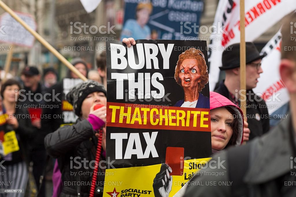 Young woman shows poster with caricature of Margaret Thatcher royalty-free stock photo