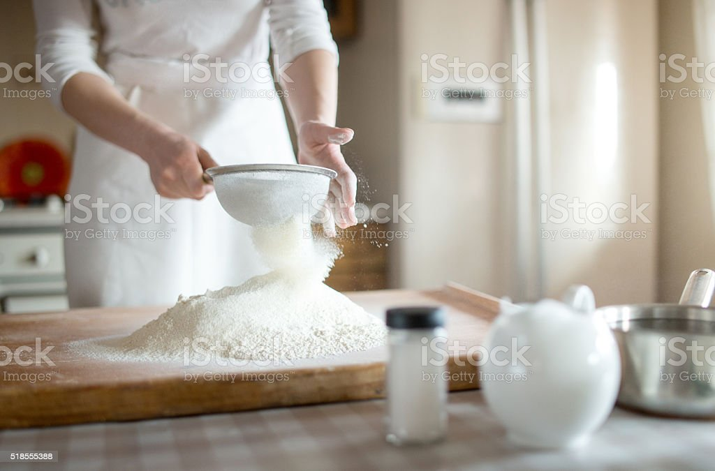 young woman sifting flour into bowl at the kitchen stock photo