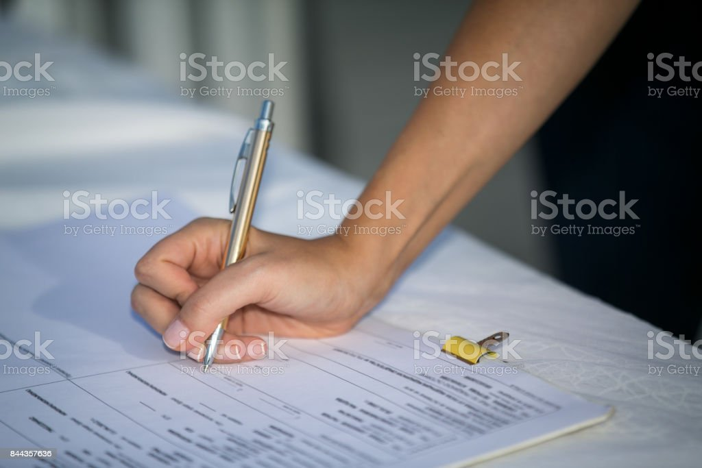 Young Woman Signing a Document stock photo