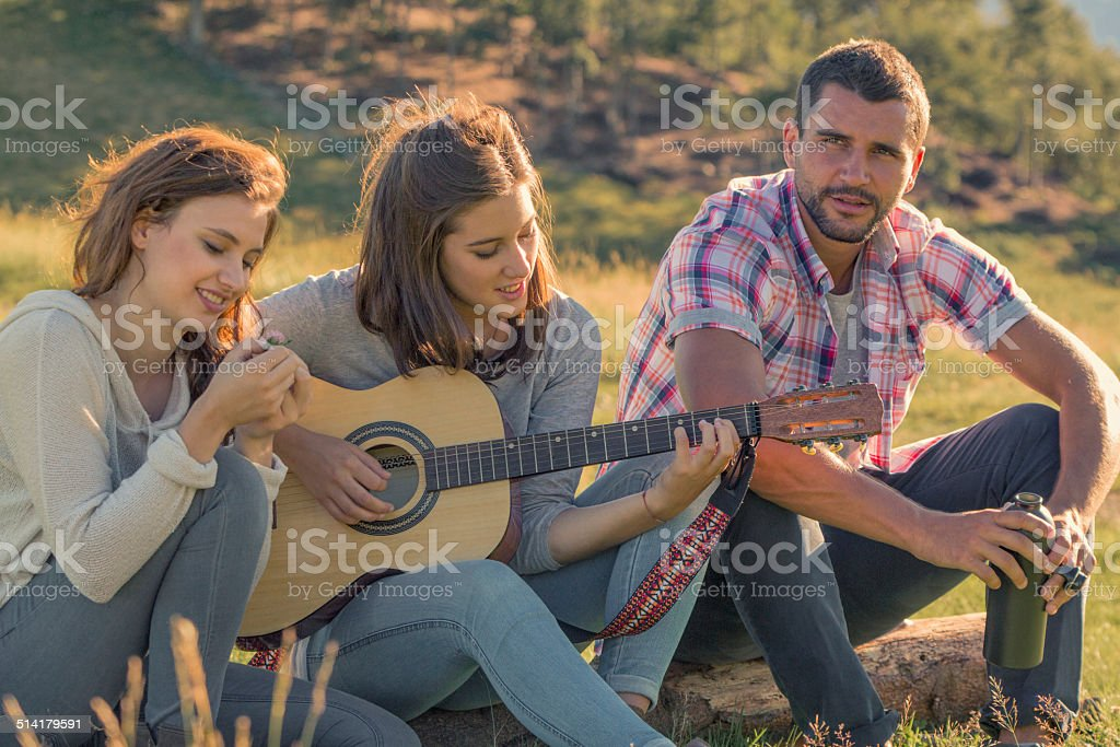 Young woman sing playing guitar with friends on sunset outdoor stock photo