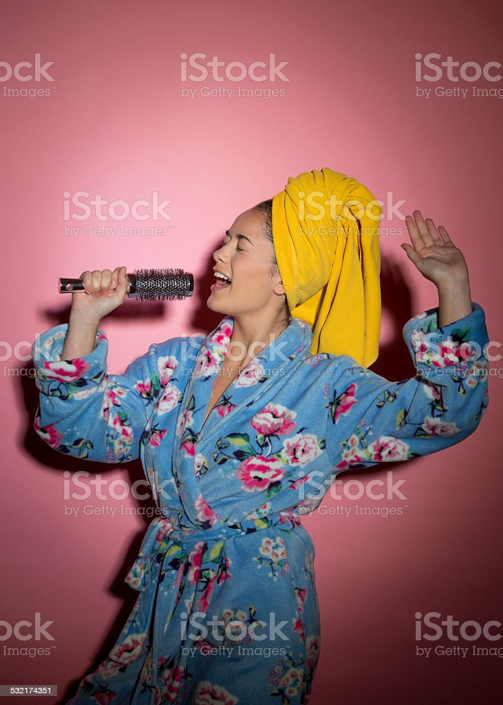 Young Woman Singing into Hairbrush stock photo