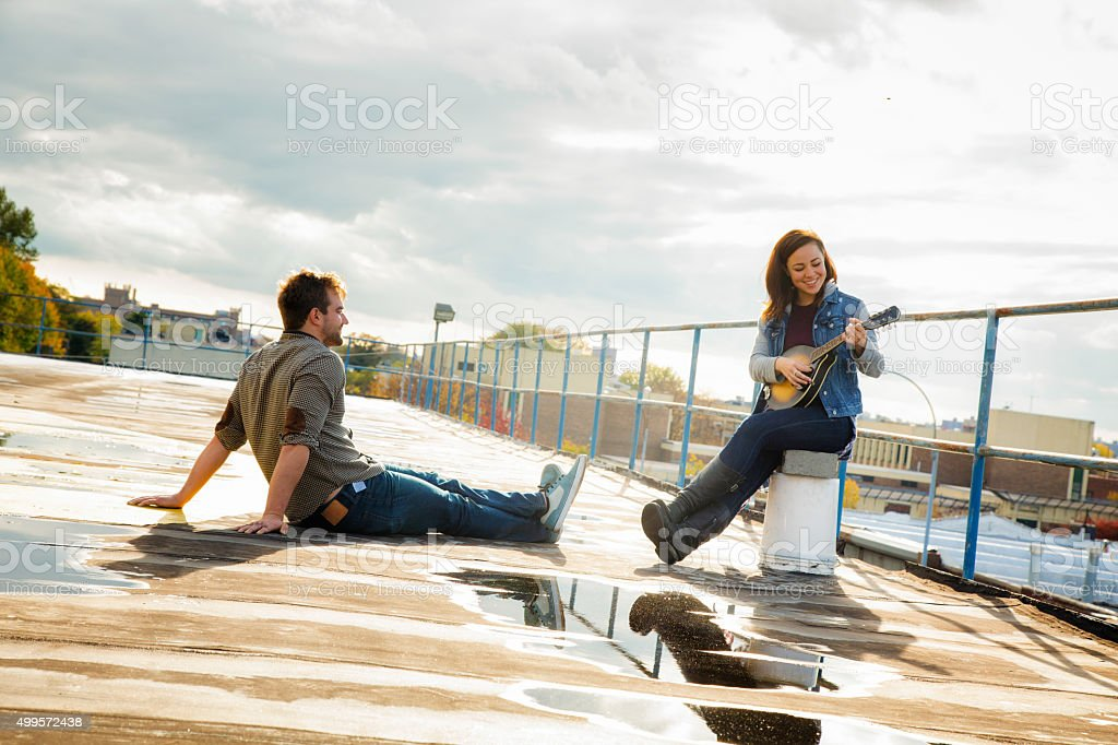 Young woman sings her new country song to male friend stock photo