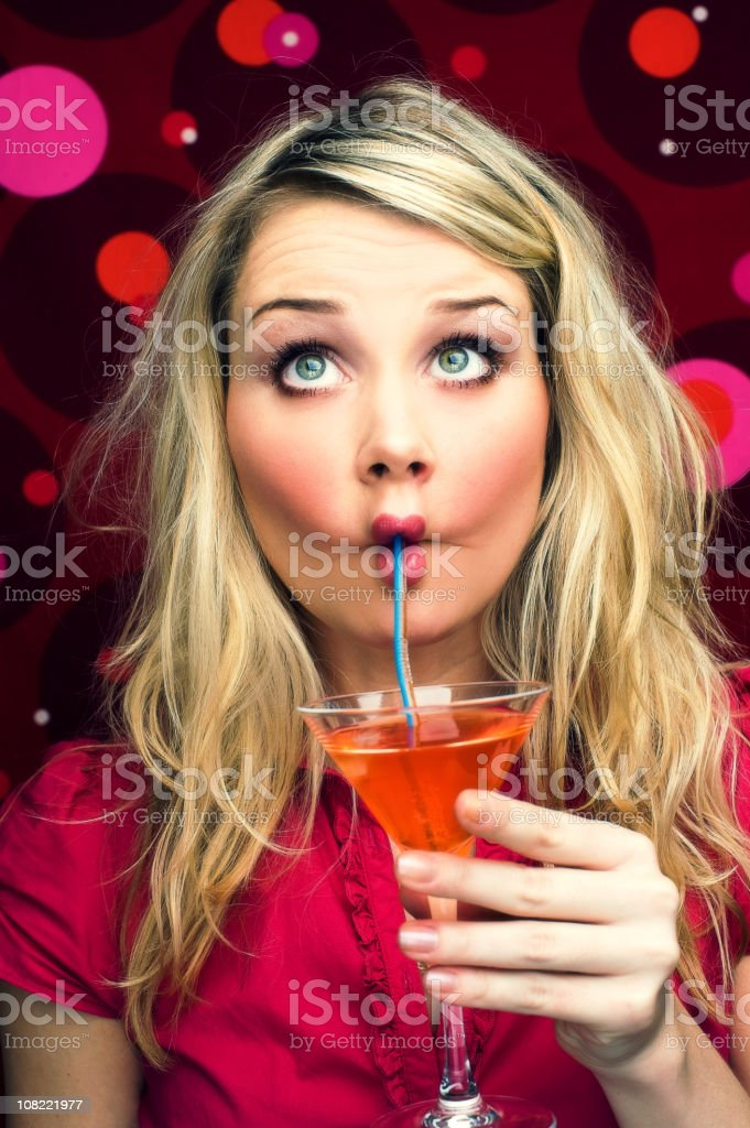 Young Woman Sipping Cocktail Through Straw stock photo