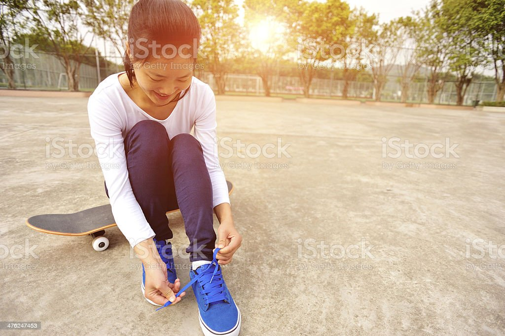young woman sit on skateboard try new shoes royalty-free stock photo