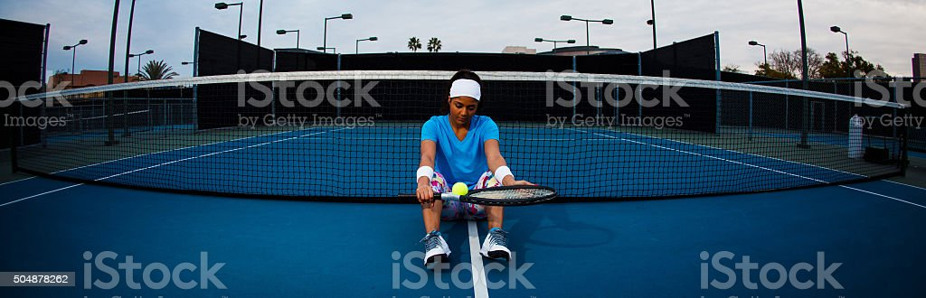 Young woman sits and rests on tennis court stock photo