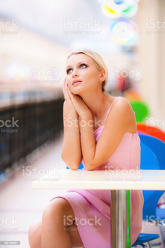 Young woman sits at little table  restaurant royalty-free stock photo