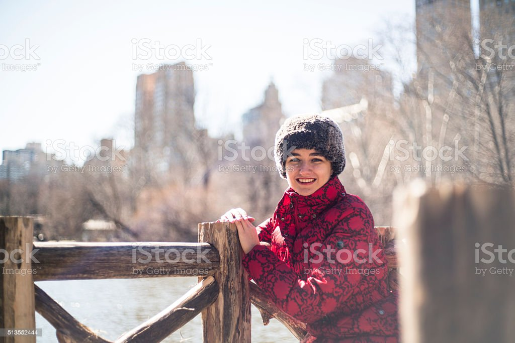 Young woman sits next to The Lake in Central Park stock photo