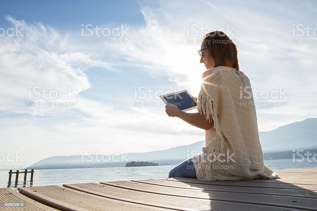 Young woman sits on jetty above lake, uses digital tablet stock photo