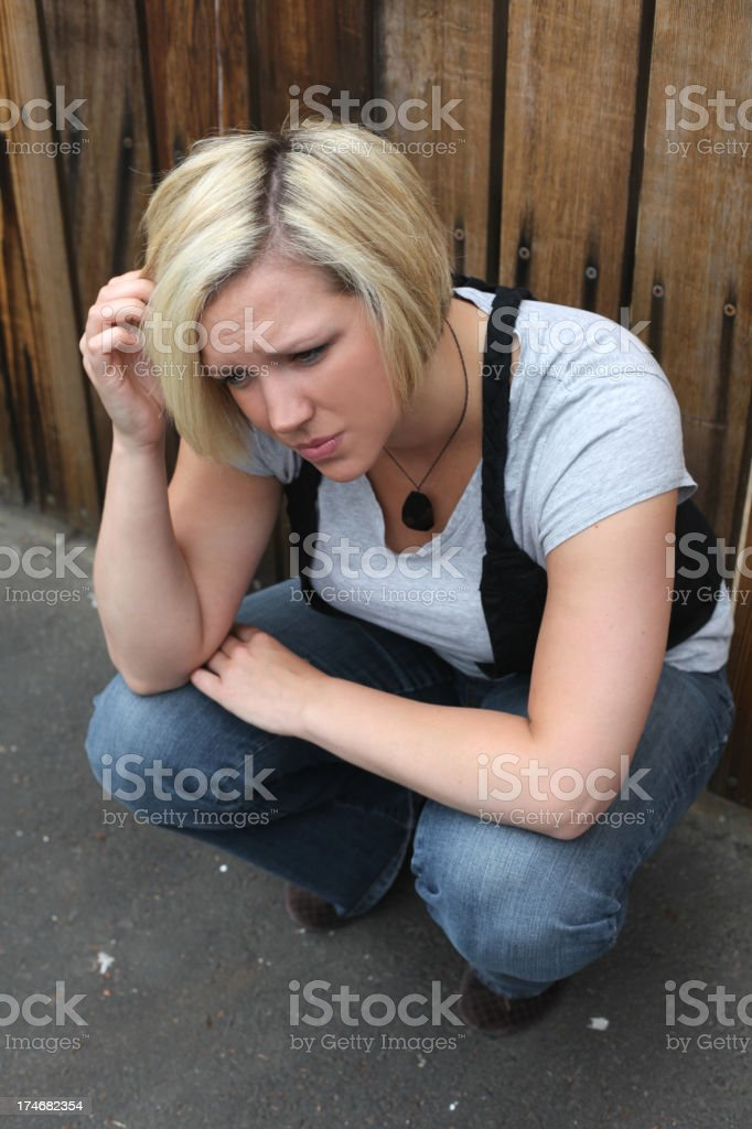 Young Woman Sits with Expression of Anxiety royalty-free stock photo
