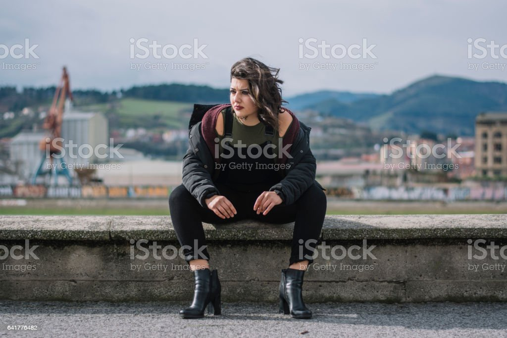 Young woman sittin on the street stock photo