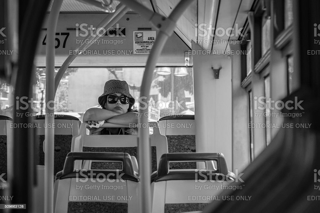 Young woman sitting alone at the back of a bus stock photo