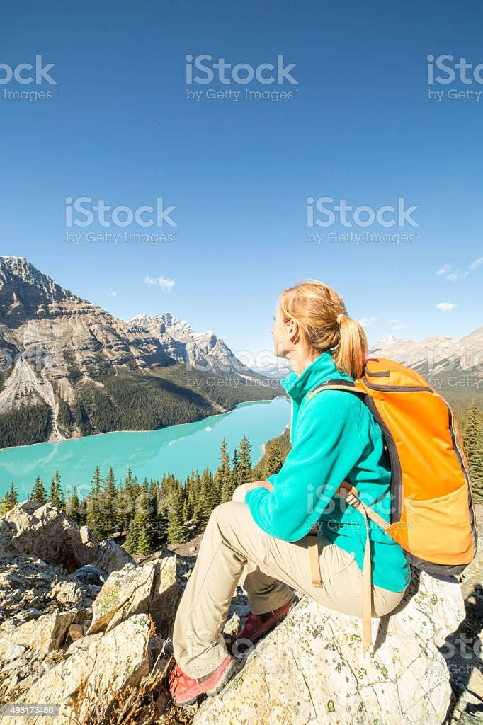young woman sitting and admiring view from mountain top stock photo